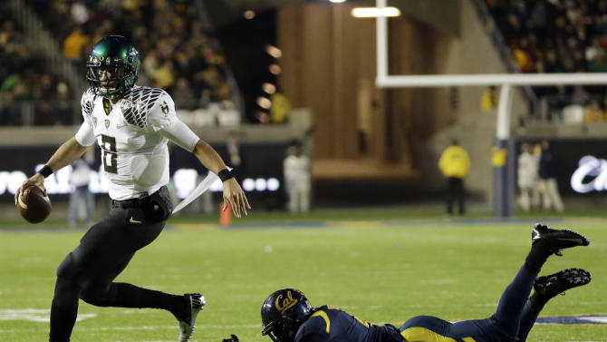 Oregon quarterback Marcus Mariota, left, runs past a California defender during the first half of an NCAA college football game in Berkeley, Calif., Saturday, Nov. 10, 2012. (AP Photo/Marcio Jose Sanchez)
