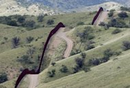 <p>A U.S. Customs and Border Patrol agent drove along the international border fence near Nogales, Ariz in September 2010. (AP Photo/Matt York)</p>