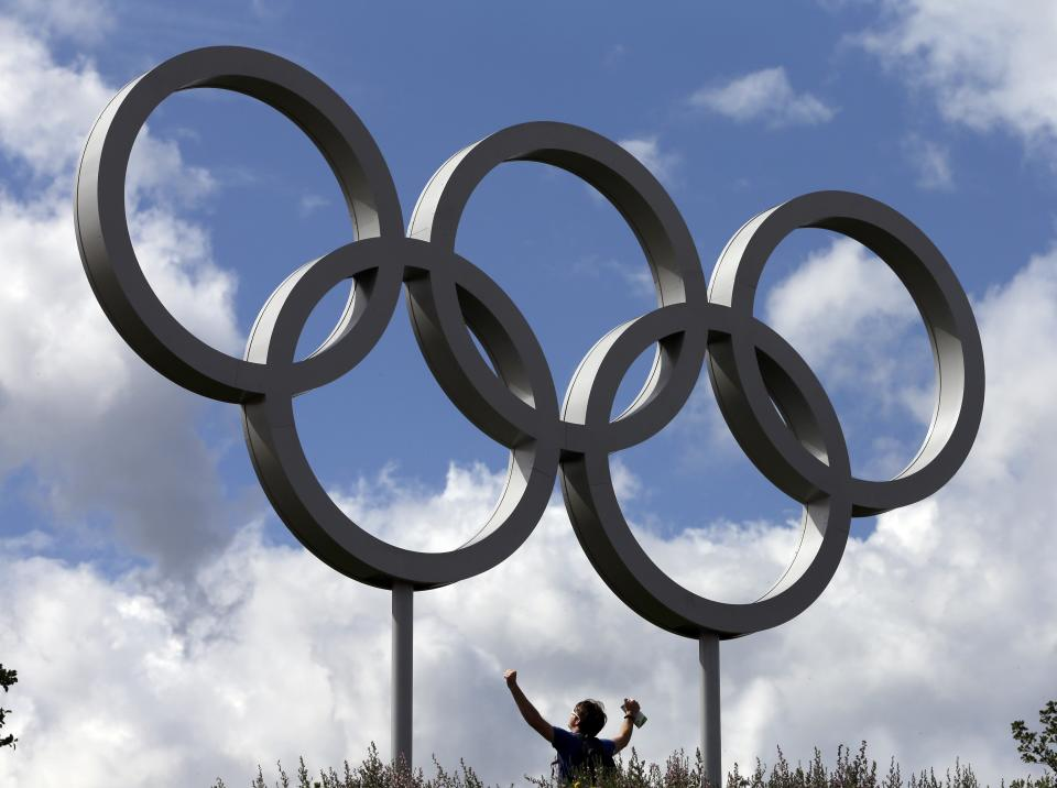 A spectator poses for a photo under the Olympic rings inside of the Olympic Park at the 2012 Summer Olympics, Sunday, July 29, 2012, in London. (AP Photo/Darron Cummings)