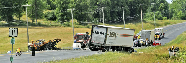 Emergency personnel investigate the scene of a fiery chain-reaction crash in a roadwork zone on Route 11 Thursday, July 19, 2012 in Antwerp, N.Y. Police say a tractor-trailer driven by James A. Mills 