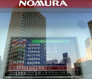 An electronic share price board at a Nomura Securities&#39; branch in Tokyo. Tokyo&#39;s bourse imposed a record fine of about $2.5 million on Nomura Holdings on Wednesday in the wake of an insider trading scandal at Japan&#39;s biggest brokerage