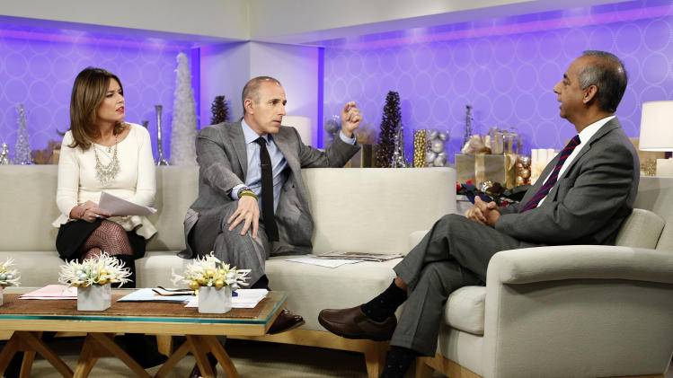 "This image released by NBC shows co-hosts Savannah Guthrie, left, and Matt Lauer, center, during an interview with freelance photographer R. Umar Abbasi on NBC News' ""Today"" show, Wednesday, Dec. 5, 2012 in New York. On Monday, Abbasi took a photo of a man who was pushed onto a New York subway track and killed after being hit by a train. The New York Post published the photo on its front page Tuesday showing the man with his head turned toward the oncoming train. The headline read in part: ""This man is about to die."" (AP Photo/NBC, Peter Kramer)"