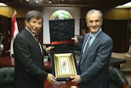 Turkish Foreign Minister Ahmet Davutoglu (left) receives a souvenir from the governor of Kirkuk, Najm al-Din Omar Karim, in the disputed northern Iraqi city on August 2 during a rare visit by a high-ranking Turkish official to the city. The Iraqi foreign ministry sharply criticised the visit, saying it had not been informed of or approved the trip