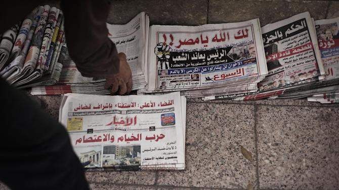An Egyptian newspaperman arranges state-owned newspapers being sold on the street in Cairo, Egypt, Tuesday, Dec. 4, 2012. Most independent Egyptian newspapers suspended publication of Tuesday's edition in protest over the hurried drafting of the country's new constitution adopted by an Islamist-led panel. The media protest involved at least eight influential dailies and was part of a planned campaign of civil disobedience that could bring in other industries and build on an ongoing strike by Egypt's judges. (AP Photo/Nariman El-Mofty)