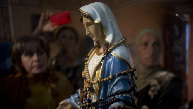 """Christian worshipers gather next to a statue of the Virgin Mary, that residents say """"weeps"""" oil, inside an apartment belonging to the Khoury family, in Tarshiha, a small town in northern Israel,Tuesday, Feb. 11, 2014. The family says it is most striking when a """"tear"""" seems to roll down the statue's cheek. It says some 2,000 people have come to see the statue over the last week. (AP Photo/Ariel Schalit)"""