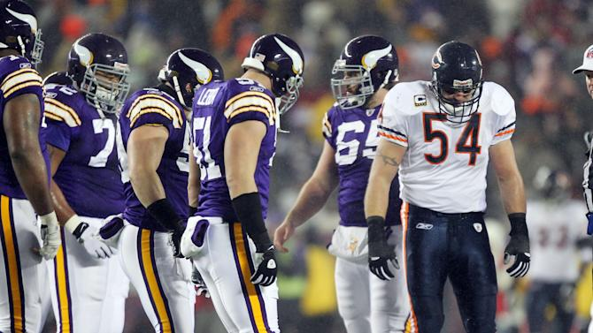 Chicago Bears' Brian Urlacher (54) looks down as Minnesota Vikings quarterback Brett Favre (4) lies on the ground after being hit during the first half an NFL football game Monday, Dec. 20, 2010, in Minneapolis. The game is being played at the University of Minnesota's TCF Bank Stadium because of damage to the Metrodome roof. (AP Photo/Andy King)