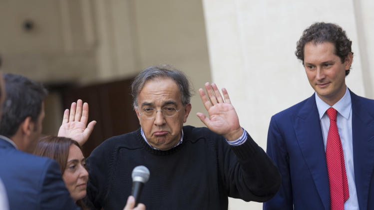 Italian Premier Matteo Renzi, left, passes a reporter's microphone to CEO of Chrysler and Fiat, Sergio Marchionne, center, to answer a question as Fiat Chairman John Elkann, looks on during the 2015 Jeep Renegade presentation, at Chigi palace, Premier's office, in Rome, Friday, July 25, 2014. (AP Photo Alessandra Tarantino)