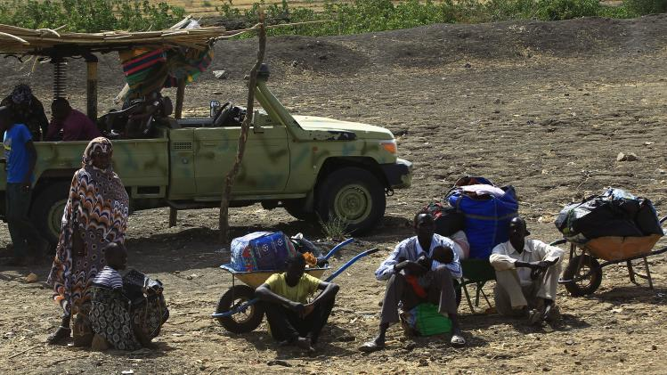 South Sudanese fleeing an attack on the South Sudanese town of Rank, wait with their belongings after arriving at a border gate in Joda, along the Sudanese border