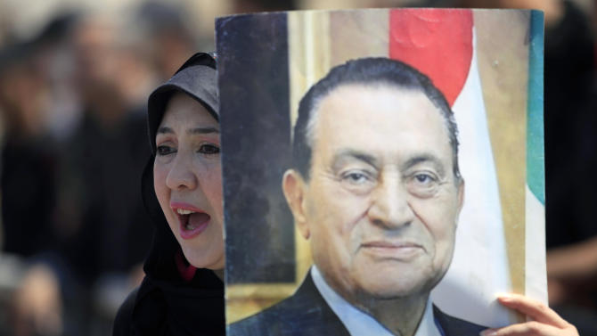 A supporter of Egypt's ousted President Hosni Mubarak, pictured, rally outside a courtroom in Cairo, Saturday, May 11, 2013. Egyptian prosecutors say they are presenting new evidence in the retrial of Mubarak. The former president, all in white and wearing sunglasses, attended the hearing in the courtroom defendants' cage alongside his two sons and former interior minister, who was in charge of police at the time. (AP Photo/Khalil Hamra)
