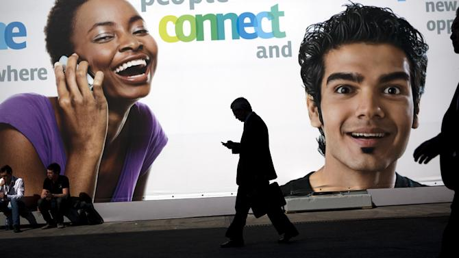 A visitor uses his mobile phone as he is seen next to a big banner announcing new mobiles at the world's largest mobile phone trade show in Barcelona, Spain, Thursday March 1, 2012. (AP Photo/Emilio Morenatti)