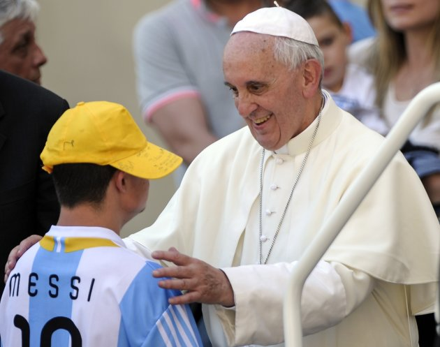 Pope Francis smiles as he talks with a sick youth after the weekly audience in Saint Peter's Square at the Vatican