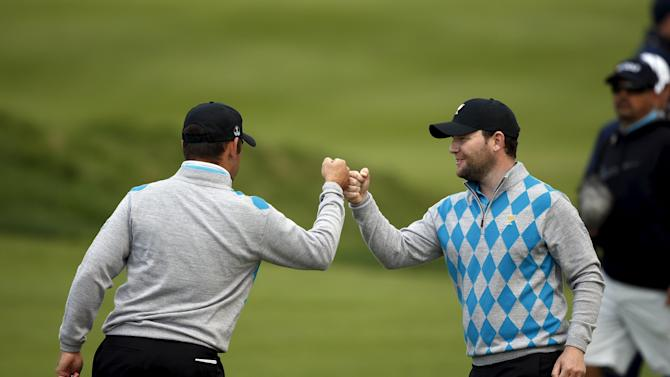 International team member Oosthuizen shares a fist bump with Grace after sinking a putt to defeat U.S. team members Reed and Fowler during the foursome matches of the 2015 Presidents Cup golf tournament in Incheon, South Korea