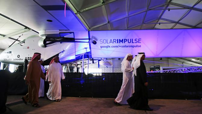 Emirati officials walk past a Swiss-made solar-powered aircraft during the Solar Impulse presentation at the Al Bateen airport in Abu Dhabi, United Arab Emirates, Tuesday, Jan. 20, 2015. The founders of a Swiss-made solar-powered aircraft that is attempting to fly around the world say their journey will include stops in India, China and the United States after it takes off as early as next month. (AP Photo/Kamran Jebreili)