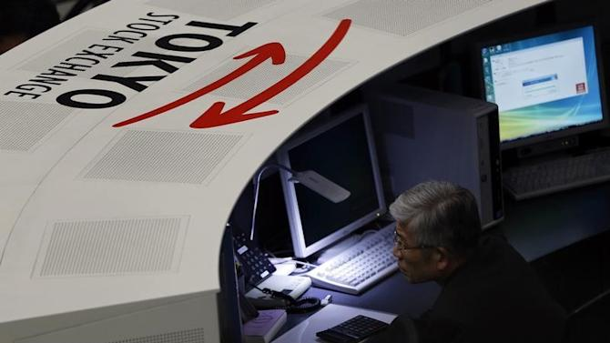 An employee of the Tokyo Stock Exchange (TSE) looks at a monitor at the bourse at the TSE in Tokyo