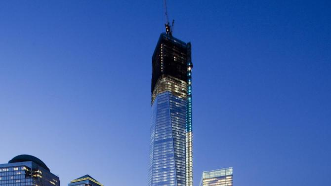 FILE - In this file photo of Sept. 6, 2012, One World Trade Center, now up to 105 floors, rises above the National September 11 Memorial and Museum in New York. Eleven years after terrorists attacked the World Trade Center, the new World Trade Center now dominates the lower Manhattan skyline. (AP Photo/Mark Lennihan, File)