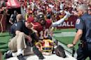 Washington Redskins quarterback Robert Griffin III (10) leaves the game on a cart after injuring his left ankle during the first half of an NFL football game against the Jacksonville Jaguars on Sunday, Sept. 14, 2014, in Landover, Md. (AP Photo/Nick Wass)