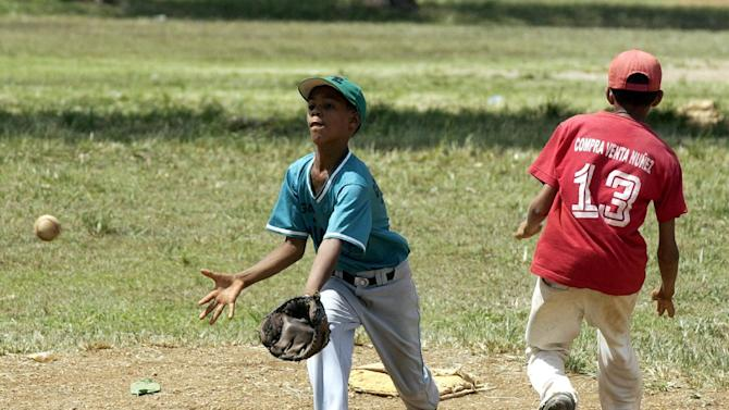 Dauri Javier Aguirro, 10, left, waits for a late throw as Ale Veloz, 13, steals second Thursday, July 31, 2003 at the Complejo Deportivo baseball camp in San Pedro de Macoris, Dominican Republic. The host country of the Pan American games is hoping to prove its baseball superiority by taking the gold medal. The small town, about 40 miles east of Santo Domingo, has sent hundreds of players to the major leagues, including Sammy Sosa. The Pan American games begin August 1. (AP Photo/Joe Cavaretta)