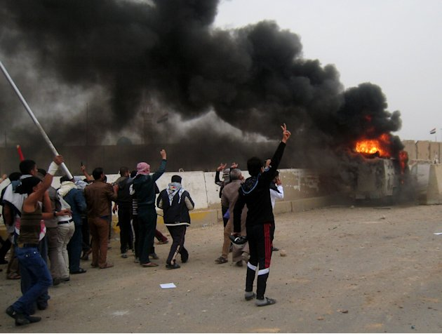 Protesters chant slogans against Iraq's Shiite-led government near a burning Iraqi army armored vehicle during clashes in Fallujah, 40 miles (65 kilometers) west of Baghdad, Iraq, Friday, Jan. 25, 201