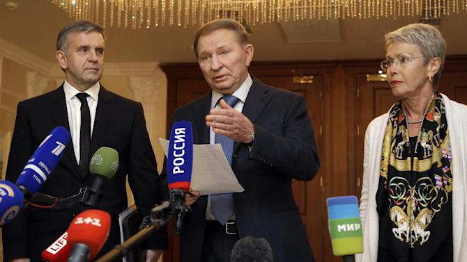 From left, Russian Ambassador to Ukraine Mikhail Zurabov, former Ukrainian President Leonid Kuchma and the Organization for Security and Cooperation in Europe (OSCE) envoy Heidi Tagliavini, meet with the media after peace talks in Ukraine in Minsk, Belarus, early Saturday, Sept. 20, 2014. Participants in Ukrainian peace talks agreed early Saturday to create a buffer zone to separate government troops and pro-Russian militants and withdraw foreign fighters and heavy weapons from the area of conflict in eastern Ukraine. (AP Photo/Sergei Grits)