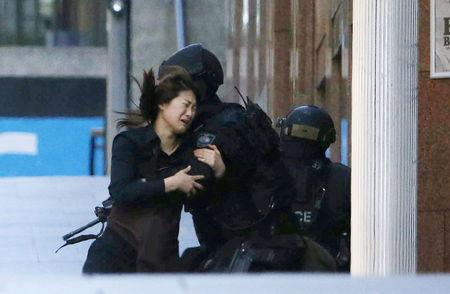 File photo of a hostage running towards a police officer in central Sydney