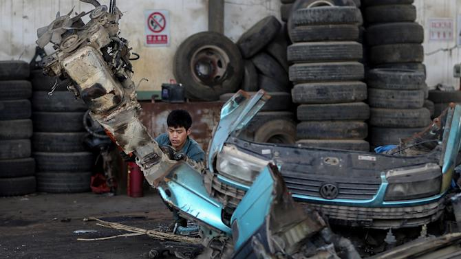 A man disassembles a scrapped car at a recycling station in Kunming