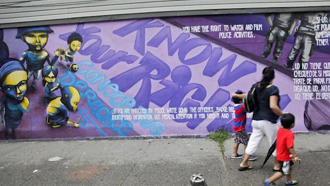 "FILE - In this July 18, 2012 photo, A woman and children walk past a street mural depicting individual rights during a ""Stop and Frisk"" on in New York. The New York City Council Public Safety Committee will hear proposals to impose new requirements for police ""stop-and-frisk"" encounters, a strategy of detaining and sometimes searching anyone officers deem suspicious, but critics argue the practice is discriminatory and unfairly targets minorities. (AP Photo/Bebeto Matthews, File)"
