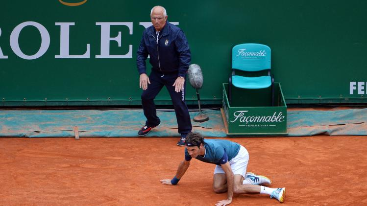 Federer of Switzerland falls during his men's singles final match against compatriot Wawrinka at the Monte Carlo Masters tennis tournament in Monaco