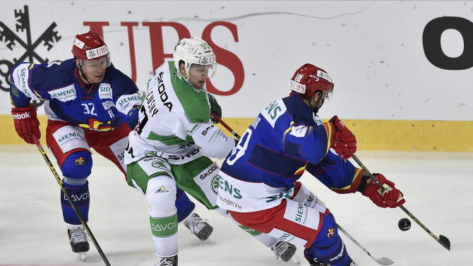Helsinki's Riku Hahl, left, and Semir Ben Amor, right, challenge  for the puck with  Ufa's Alexei Vasilevsky during the game between Finland's Jokerit Helsinki and Russia's HC Salavat Yulaev Ufa at the 88. Spengler Cup hockey tournament in Davos, Switzerland, Saturday, Dec. 27, 2014. (AP Photo/Keystone,Peter Schneider)