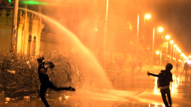 Egyptian protesters throw stones while security police open water cannons on them from inside the grounds of the presidential palace during a demonstration in Cairo, Egypt, Monday, Feb. 11, 2013. Security forces sprayed protesters with water hoses and tear gas outside the presidential palace Monday as Egyptians marked the second anniversary of autocrat Hosni Mubarak's ouster with angry demonstrations against his elected successor.(AP Photo/Khalil Hamra)