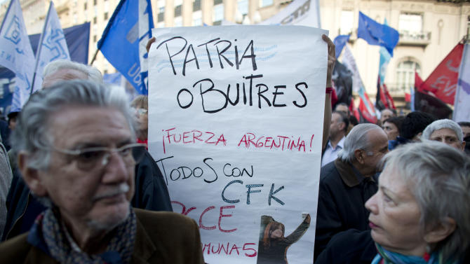 "An activist holds a banner that reads in Spanish ""Homeland or vultures, be strong Argentina"""