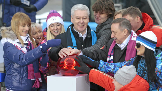 Moscow's Mayor Sergei Sobyanin, center, surrounded by various officials, sport enthusiasts and entertainers hits a symbolic button to launch the one-year count down clock for the upcoming 2014 Sochi Olympics, in Moscow, Russia, Thursday, Feb. 7, 2013. (AP Photo/Mikhail Metzel)