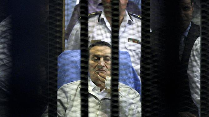 Egypt's deposed President Hosni Mubarak attends a hearing session in his retrial on appeal in Cairo, Egypt, Monday, April 15, 2013. Mubarak will remain in custody on new corruption charges despite a court order to release him on bail pending his retrial on charges related to killing of protesters in the 2011 uprising against him, Egypt's state news agency said Monday. (AP Photo/Ahmed Gomaa)