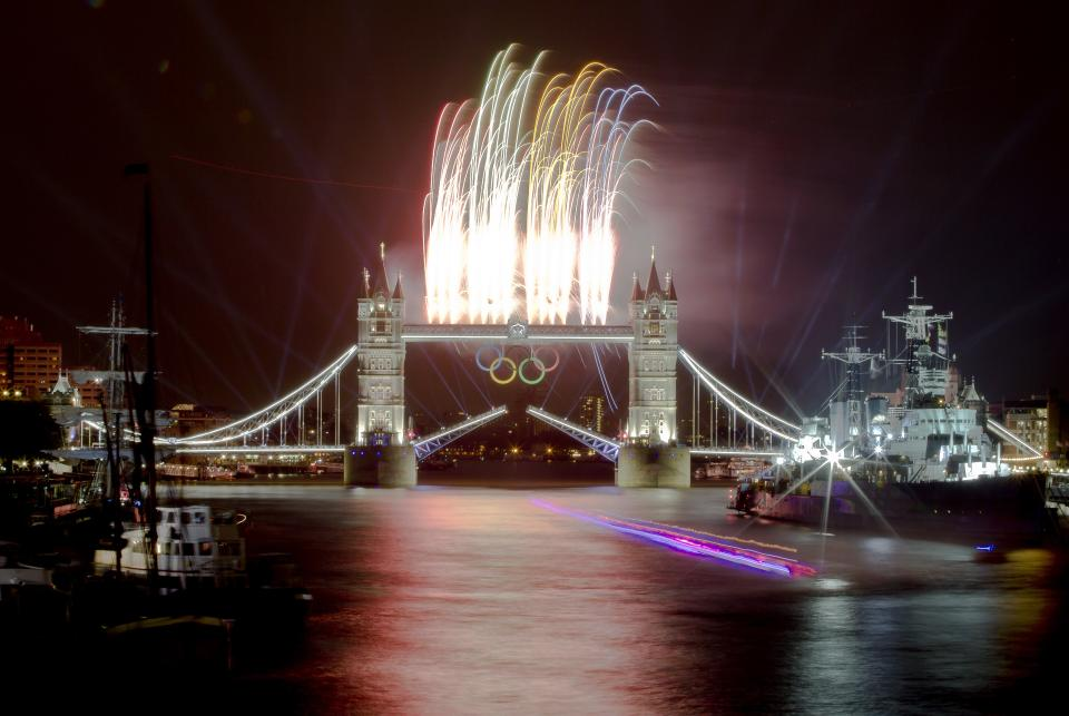 A speedboat carrying the Olympic Flame leaves a trail on this slow exposure photograph as fireworks explode above the iconic Tower Bridge over the River Thames in central London, decorated with Olympic rings, during the Opening Ceremony at the 2012 Summer Olympics, Friday, July 27, 2012, in London. (AP Photo/Vadim Ghirda)