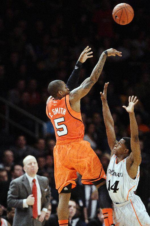 Louisville's Chris Smith (5) shoots over Cincinnati's Ge'Lawn Guyn (14) as Cincinnati head coach Mick Cronin watches during the first half of an NCAA college basketball game in the final of the Big East Conference tournament in New York, Saturday, March 10, 2012. (AP Photo/Frank Franklin II)