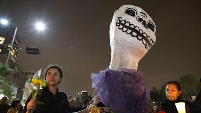 Two women stand next to a giant stylized skull during a massive march to pressure the government into finding 43 missing college students, in Mexico City,Thursday, Nov. 20, 2014. Protesters marched in the capital city to demand authorities find the 43 college students that according the federal government where tortured, killed and incinerated. Mexico officially lists more than 22 thousand people as having gone missing since the start of the country's drug war in 2006, and the search for the missing students has turned up other, unrelated mass graves. (AP Photo/Rebecca Blackwell)