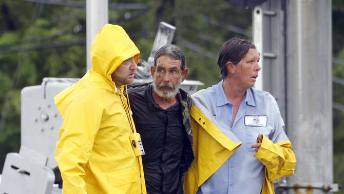 FILE - In this Thursday, Aug. 30, 2012 file photo, Larry Bailey, center, found in floodwater caused by Hurricane Isaac, is helped to safety in Slidell, La. When a Florida man saw the news photo of Bailey, who at the time was unidentified, rescued from Isaac's floodwaters, he was sure it was his brother. It wasn't — but the mistaken identity started a search that ultimately reunited Bailey, who has been homeless, with the two daughters he hadn't seen in 16 years. (AP Photo/John Bazemore, File)