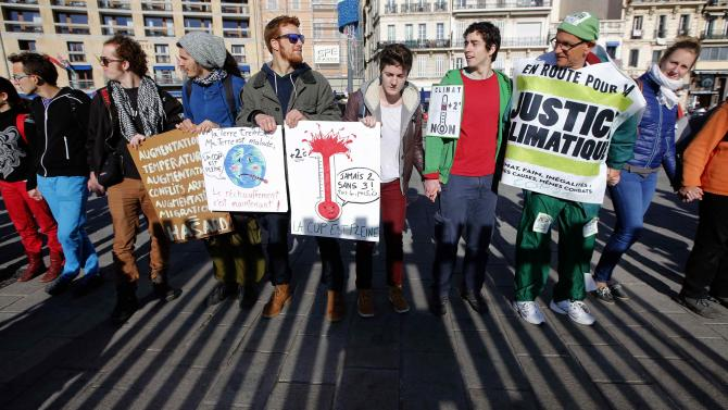 Environmental activists take part in a symbolic human chain gathering after the cancellation of a planned climate march following shootings in the French capital ahead of the World Climate Change Conference 2015 in Marseille