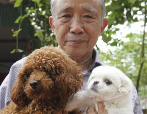 Nguyen Bao Sinh, owner of the Bao Sinh Dog-Cat Resort, poses with dogs at his resort in Hanoi
