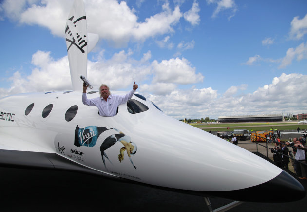British billionaire Richard Branson poses for the photographers in the window of a replica of the Virgin Galactic, which according to the company will be the worlds first commercial spaceline, at the