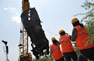 A crane removes the mangled remains of a coach of the Bangalore-bound Hampi Express after it collided with a stationary goods train near Penneconda town in Ananthpur District, about 145 kms from Bangalore