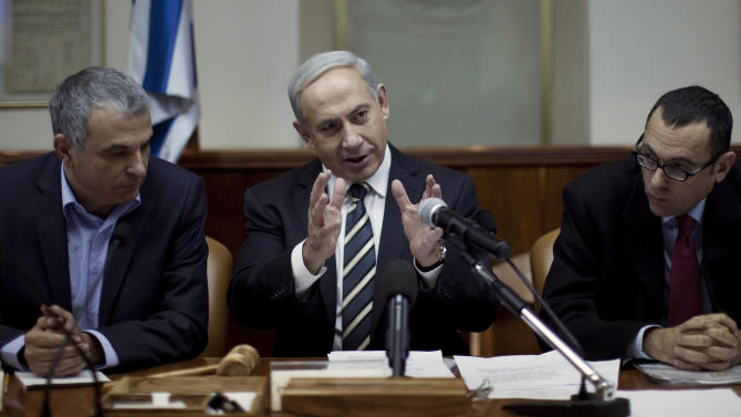 Israeli Prime Minister Benjamin Netanyahu, center, heads the weekly cabinet meeting in his Jerusalem office, Sunday, Dec. 30, 2012. Sitting left is Cabinet minister Moshe Kachlon, and Cabinet Secretary Tzvi Hauser, right. (AP Photo/Abir Sultan, Pool)