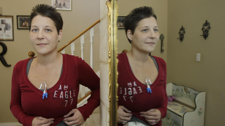 Michelle Dunaj, of Roseville, Mich., is reflected in a mirror as she poses for a photo, Tuesday, Oct. 9, 2012, at the home of friends in Bonney Lake, Wash. Dunaj, who is dying of leukemia, was making what she expects will be the last trip of her life on Oct. 2, 2012, as she departed for Hawaii through Seattle-Tacoma International Airport. Dunaj says she received a full public pat-down in the TSA security line and had to lift her shirt and pull back bandages so agents could get a good look at tubes used for feeding and medicine. Dunaj hopes her embarrassing experience will change the way the Transportation Security Administration treats travelers with medical conditions. (AP Photo/Ted S. Warren)