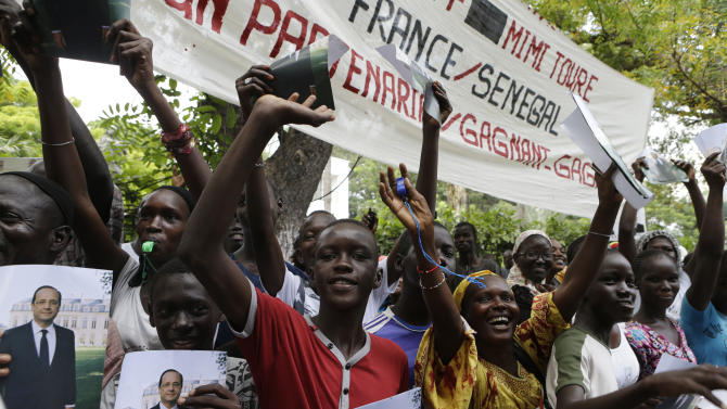 Senegalese people hold photographs of French President Francois Hollande as they cheer his arrival at the Presidential Palace in Dakar, Senegal, Friday, Oct. 12, 2012. Hollande will attempt to make right France's relationship with Africa on his first visit to the continent on Friday, beginning with a stop in Senegal, the seat of France's former colonial empire. He is set to leave Friday night for Congo, where he will attend the Francophonie summit in the capital, Kinshasa. (AP Photo/Rebecca Blackwell)