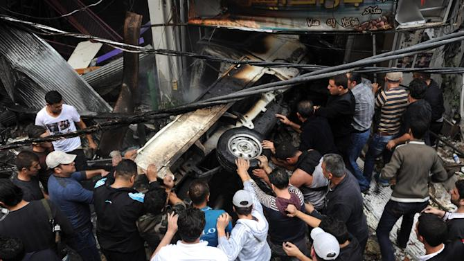 This photo released by the Syrian official news agency SANA, shows Syrians pushing a burnt car at the scene after a blast occurred according to footage and reports shown on State-run Al-Ikhbariya television in the Mazzeh al-Jabal district of the Syrian capital Damascus, Syria, Monday, Nov. 5, 2012. Several people were killed and injured, among them children, Al-Ikhbaria said. (AP Photo/SANA)