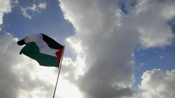 A Palestinian flag flies by a tent set up by activists  in an area known as E1, near Jerusalem, Saturday, March 23, 2013. Palestinian activists erected tents in the area known as E1 to protest Israeli plans for a new settlement in the area. (AP Photo/Majdi Mohammed)