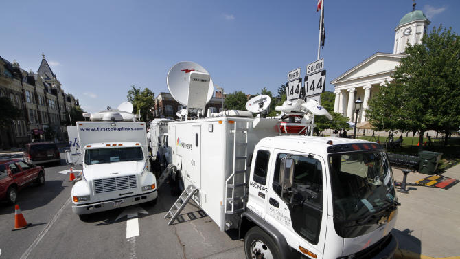 Television satellite trucks line South Allegheny Street in front of the Centre County Courthouse in Bellefonte, Pa., Sunday, June 10, 2012, in preparation for opening statements in the child sexual abuse trial of former Penn State assistant football coach Jerry Sandusky on Monday morning. (AP Photo/Gene J. Puskar)