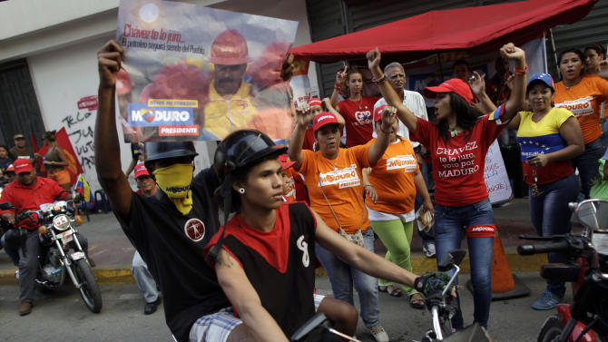 Supporters ride a motorcycle to the closing campaign rally for ruling party presidential candidate Nicolas Maduro in Caracas, Venezuela, Thursday, April 11, 2013. Maduro, the hand-picked successor of Venezuela's late President Hugo Chavez, is running for president against opposition candidate Henrique Capriles on April 14. (AP Photo/Enric Marti)