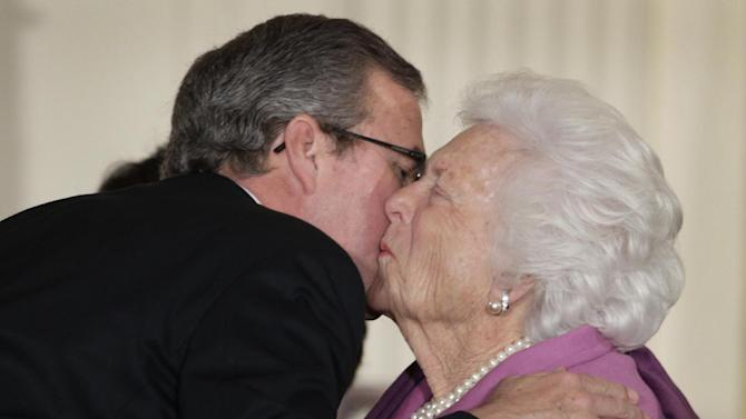 "This photo taken Feb. 15, 2011, show former Florida Gov. Jeb Bush greeting his mother, former first lady Barbara Bush, at the White House's 2010 Presidential Medal of Freedom ceremony in Washington, where her husband, former President George H.W. Bush is to receive the Medal. Jeb Bush has already heard his mother, Barbara, tell everyone ""we've had enough Bushes"" in the White House. In the lead-up to 2016 presidential campaign, the former Florida governor says he's in his 60s and doesn't have to do everything his mom says. ""I'm trying to avoid the family conversation,"" he said. (AP Photo/Carolyn Kaster, File)"