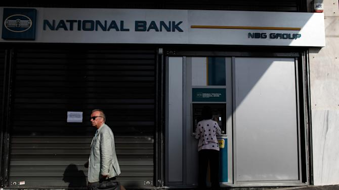 "A woman uses an ATM machine outside a closed branch of National Bank of Greece, during a 48-hour bank employee strike over austerity measures, in central Athens, on Thursday, Oct. 25, 2012. Greece's Finance Minister said the country has been granted a long-sought extension to meet the terms of its bailout program — but the claim was swiftly shot down as ""speculation"" by the European Central Bank and lead lender Germany. (AP Photo/Petros Giannakouris)"