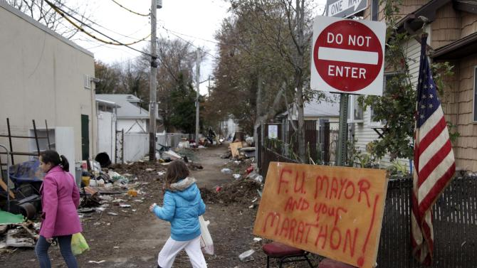 A sign about the marathon and New York City Mayor Michael Bloomberg is displayed in a devastated section of Staten Island, New York, Friday, Nov. 2, 2012.  Mayor Michael Bloomberg has come under fire for pressing ahead with the New York City Marathon. Some New Yorkers say holding the 26.2-mile race would be insensitive and divert police and other important resources when many are still suffering from Superstorm Sandy. The course runs from the Verrazano-Narrows Bridge on hard-hit Staten Island to Central Park, sending runners through all five boroughs. The course will not be changed, since there was little damage along the route. (AP Photo/Seth Wenig)